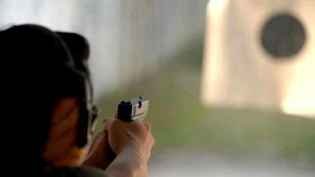 slo mo - two shots shooting handgun pistol at target range - стрелять стоковые видео и кадры b-roll