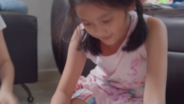Video Two sibling Asian girl drawing and painting her art and craft in the living room while staying at home. They enjoy and fun using watercolor and brush to create art project in to white paper form her imagination. Art and crafts concepts.