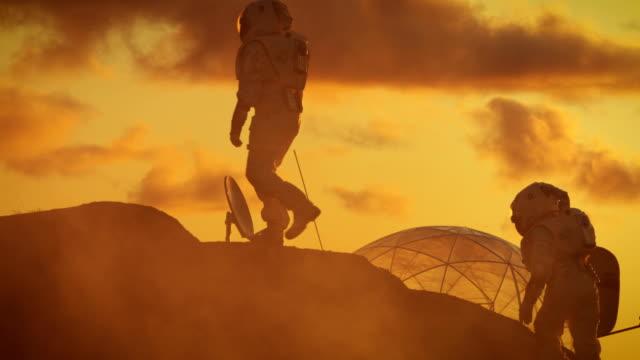 två silhuetter av astronauterna utforska röda rocky främmande planet. i bakgrunden solnedgången med bas / research station. - mars bildbanksvideor och videomaterial från bakom kulisserna