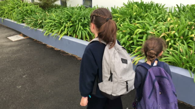 Two sister girls walking together to school video