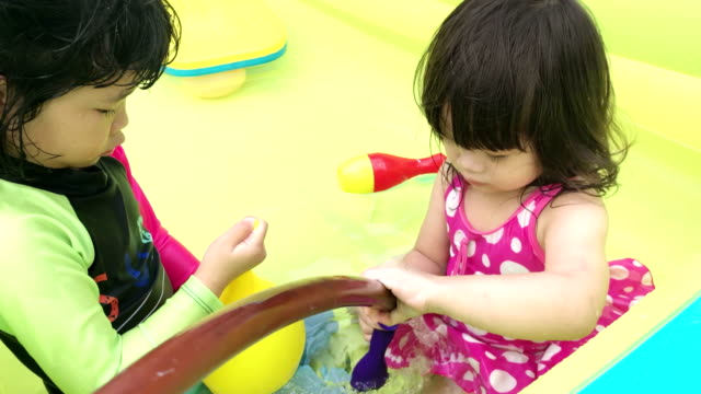 Two sister playing around in their inflatable pool together video