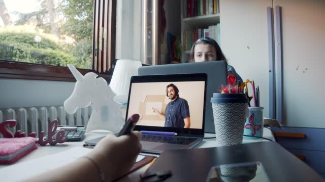 stockvideo's en b-roll-footage met twee zusters studeren samen thuis, delen een bureau om deel te nemen aan online schoollessen met laptops - corona scherm