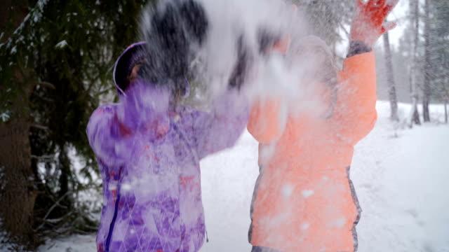 vídeos y material grabado en eventos de stock de dos hermanas se divierten con la nieve en las vacaciones de invierno - nieve amontonada