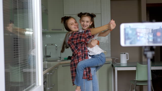 vídeos de stock e filmes b-roll de two sisters having fun and dancing in the kitchen, shooting himself in the video to the smartphone for video blog. - tv e familia e ecrã