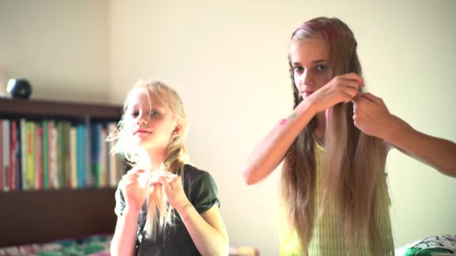vídeos de stock e filmes b-roll de two sisters in kids room, oldest sister make hair dress. - cabelo louro