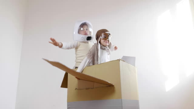 vídeos de stock e filmes b-roll de two sisters in the bedroom dressed as an aviator and astronaut, pretends to drive a paper airplane and imagines she is flying free in the sky. - crianças todas diferentes