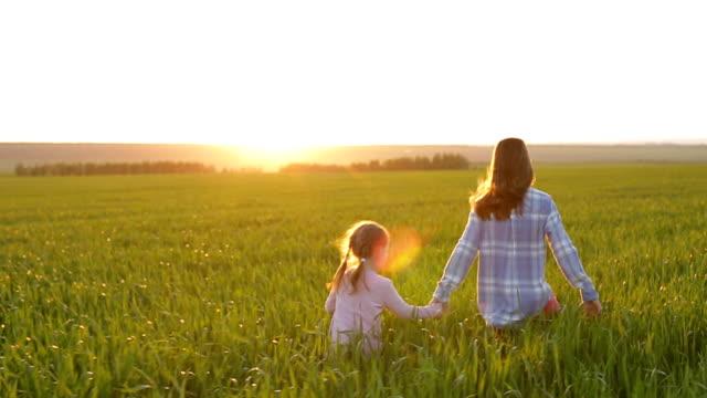 iki kız kardeş gün batımında köy yolu boyunca koşmak, kızlar yürümek - i̇nsan sırtı stok videoları ve detay görüntü çekimi