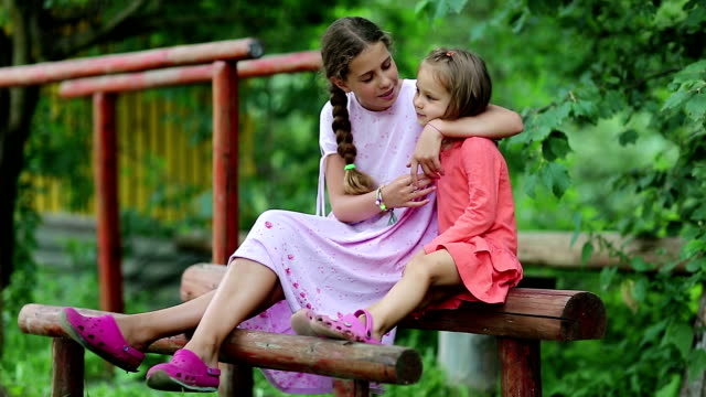 Two sisters sits on a wooden log at a sports ground and embraces video