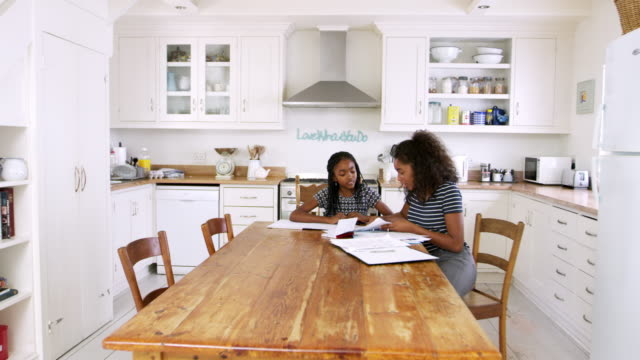 Two Sisters Sitting At Table In Kitchen Doing Homework video