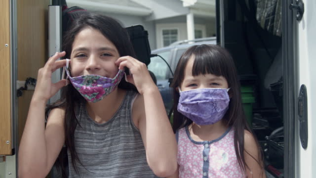 two sisters, the oldest helping the youngest put on her covid-19 mask - vestirsi video stock e b–roll