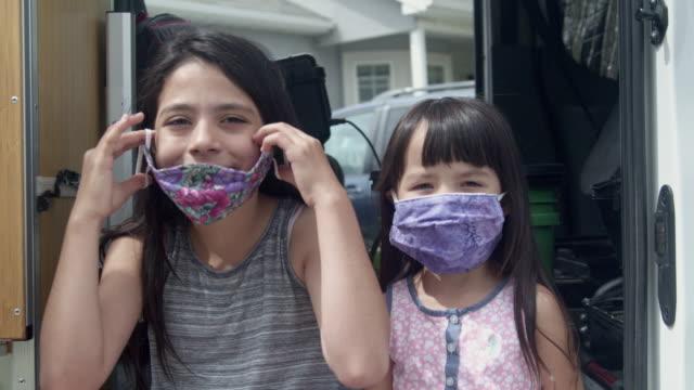 two sisters, the oldest helping the youngest put on her covid-19 mask - nakładać filmów i materiałów b-roll