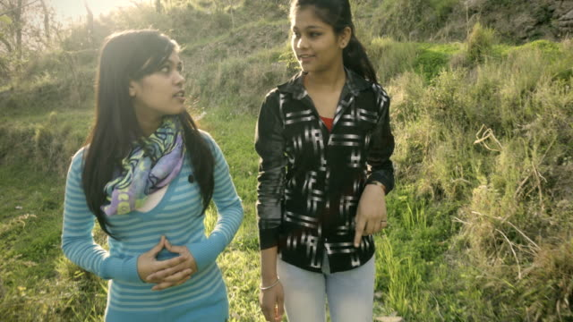Two sisters together talking and enjoying in fresh air. Outdoor video in natural sunshine of two sisters of Indian ethnicity talking and enjoying fresh air together in nature. The 4k Video shot through handheld mechanical stabilizer. sister stock videos & royalty-free footage