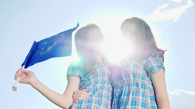 Two sisters twins with the flag of the European Union. Look at the camera, smile video