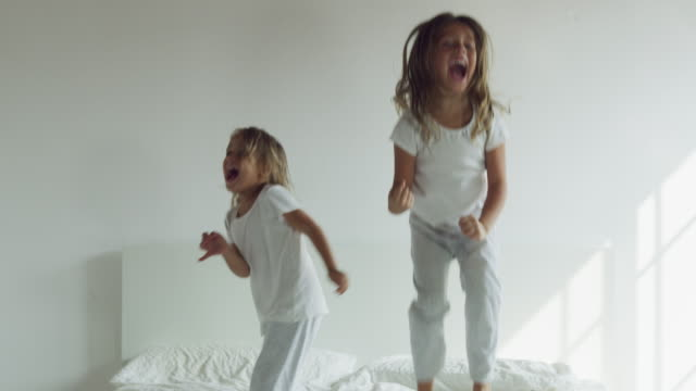 Two sisters, wearing white pajamas, jump on the bed and have fun.