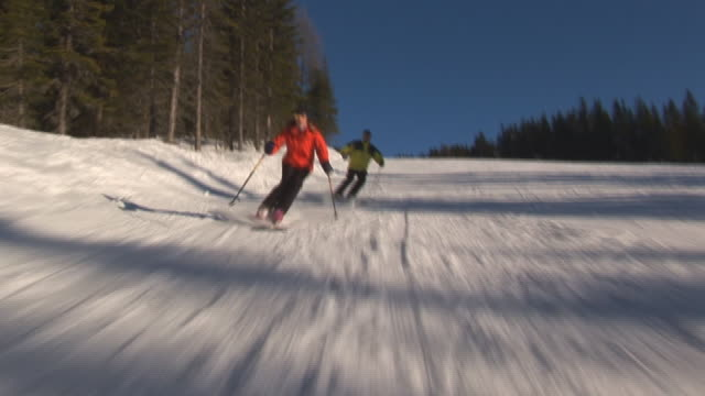 two skiers on empty slope video