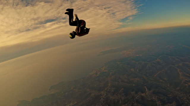 POV Two skydivers enjoying in air over coastline at sunset