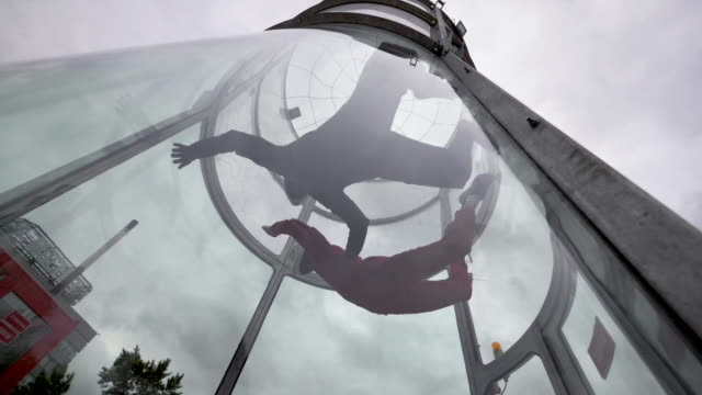 Two skydivers fly into wind tunnel. Tandem flight skydivers in wind tunnel video