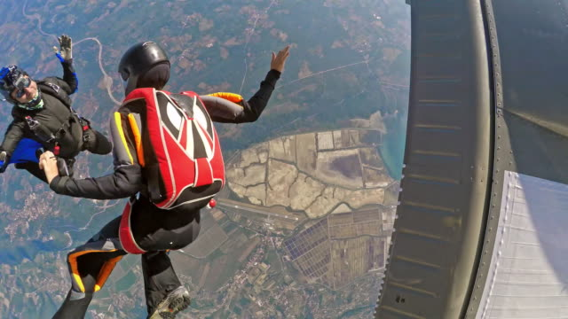 POV Two skydivers jumping off plane