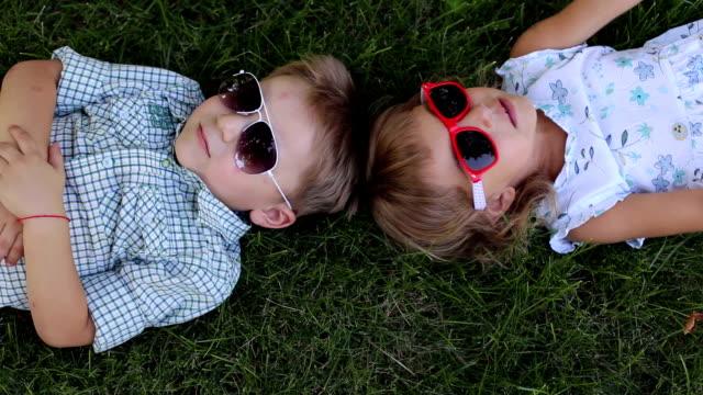 zwei kleine kinder in sonnenbrillen liegen auf dem rasen im park. blick von oben. - sonnenbrille stock-videos und b-roll-filmmaterial
