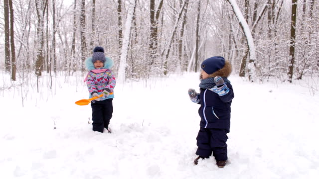 Two small children playing in winter Park. video