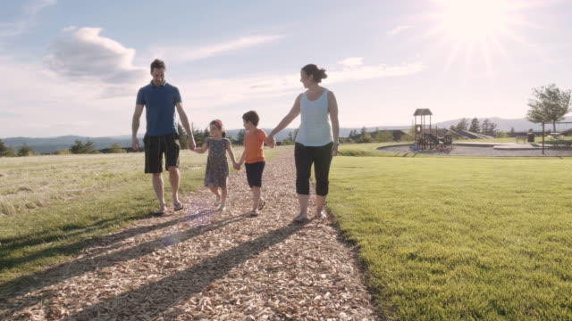 Two small kids and their parents out for a walk video