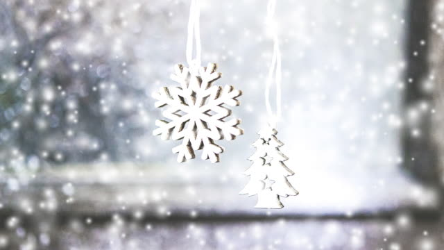 Two small white Christmas trees toys hanging on the background of a gray wall video