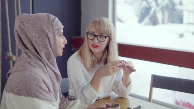 två smiley kvinnor tillbringar tid i ett kafé. - anständig klädsel bildbanksvideor och videomaterial från bakom kulisserna