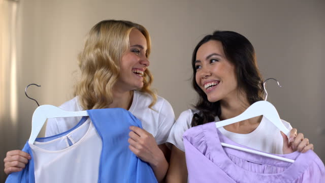 vídeos y material grabado en eventos de stock de dos sonrientes amigas eligiendo ropa en comercial moll, apta habitación, outfit - baile de estudiantes de secundaria