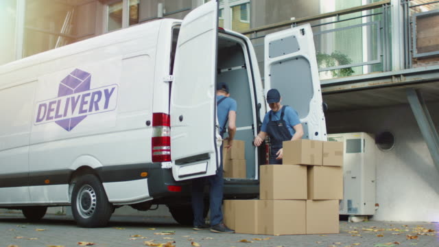 Two Smiling Movers are Loading Cargo Van with Cardboard Boxes in a Modern City. video
