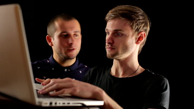 two smiling startup businessmen discussing sharing laptop computer isolated black portait video