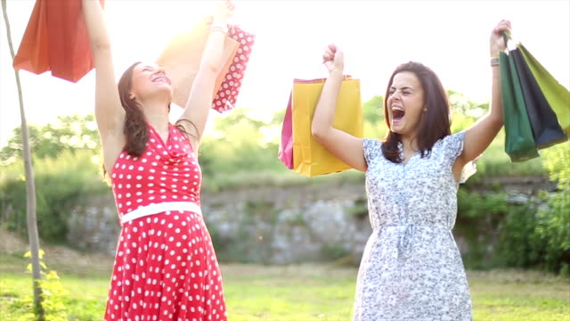 two smiling teenage girls with shopping bags video
