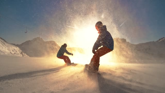 SLO MO TS Two snowboarders riding down a slope towards the sun Slow motion wide tracking shot of a man and a woman riding down the mountain and towards the setting sun and causing snow particles to fly in the air. Shot in Slovenia. recreational pursuit stock videos & royalty-free footage