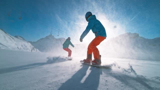 slo mo ts två snowboardåkare rida ner pisten i solsken och orsakar snö partiklar att flyga i luften - vintersport bildbanksvideor och videomaterial från bakom kulisserna