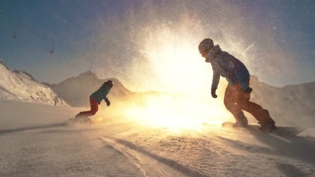 SPEED RAMP Two snowboarders riding towards the setting sun Wide speed ramp tracking shot of two snowboard riders riding towards the setting sun with snow particles flying in the air. Shot in Slovenia. holiday stock videos & royalty-free footage