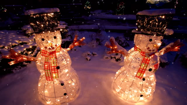 Two snowmen at night with gentle falling snow video