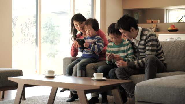 スマートフォンを使用して 2 つの息子、デジタルタブレットを使用している pc - 家族 日本人点の映像素材/bロール