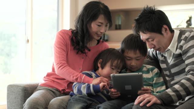 スマートフォンを使用して 2 つの息子、デジタルタブレットを使用している pc - パソコン点の映像素材/bロール