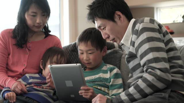 スマートフォンを使用して 2 つの息子、デジタルタブレットを使用している pc - 日本人のみ点の映像素材/bロール
