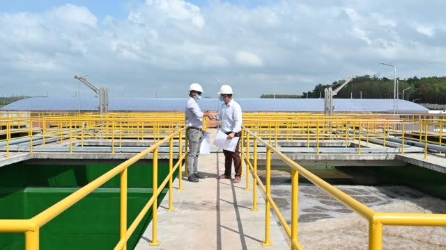 two south east asian engineers discussing and talking on blueprint at sewage treatment plant - acquedotto video stock e b–roll