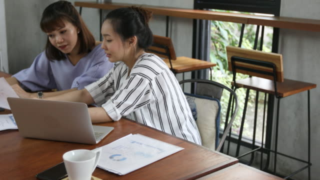 2 つの話している東南アジア女性とカフェで働く - オフィス外勤務点の映像素材/bロール
