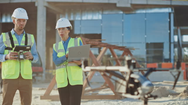 Two Specialists Controlling Drone on a Construction Site. Architectural Engineer and Safety Engineering Inspector Fly Drone on Commercial Building Construction Site Controlling Design and Quality video