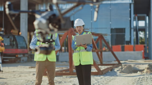 Two Specialists Controlling Drone on Construction Site. Architectural Engineer and Safety Engineering Inspector Fly Drone on Building Construction Site Controlling Quality. Focus on Drone Two Specialists Controlling Drone on Construction Site. Architectural Engineer and Safety Engineering Inspector Fly Drone on Building Construction Site Controlling Quality. Focus on Drone guidance stock videos & royalty-free footage