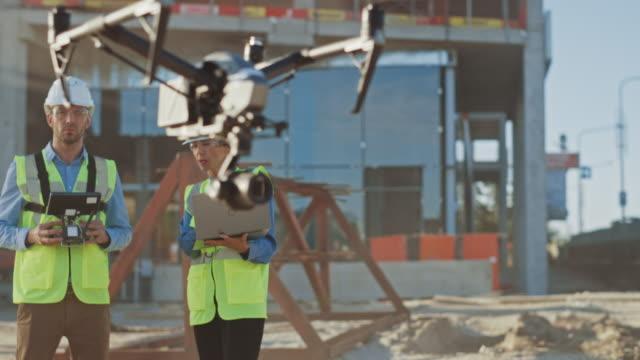 2人の専門家が建設現場でドローンを使用しています。建築技術者と安全工学検査官は、品質を制御する建築現場でドローンを飛ばします。ドローンに焦点を当てる - コントロール点の映像素材/bロール