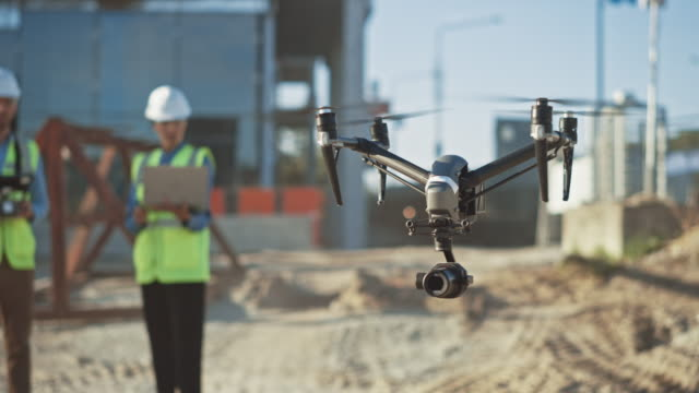 Two Specialists Use Drone on Construction Site. Architectural Engineer and Safety Engineering Inspector Fly Drone on Commercial Building Construction Site Controlling Design and Quality. Focus on Drone