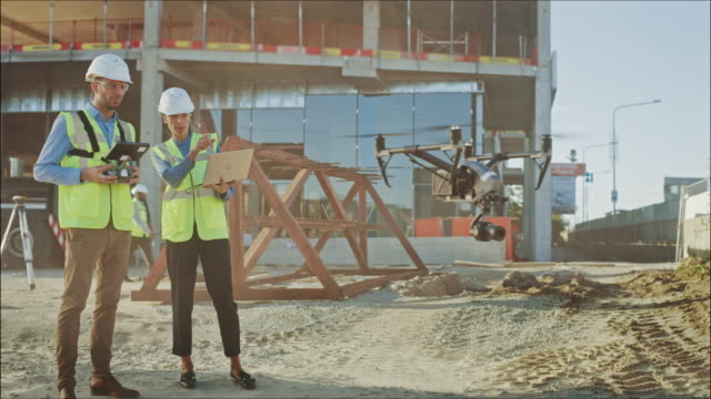 Two Specialists Using Drone on a Construction Site. Architectural Engineer and Safety Engineering Inspector Fly Drone on Commercial Building Construction Site Technical Control of Design and Quality Two Specialists Using Drone on a Construction Site. Architectural Engineer and Safety Engineering Inspector Fly Drone on Commercial Building Construction Site Technical Control of Design and Quality guidance stock videos & royalty-free footage