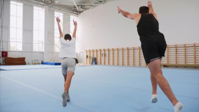 vídeos y material grabado en eventos de stock de dos deportistas haciendo una rueda de carro y un doble giro hacia atrás, steadicam, cámara lenta. - gimnasia
