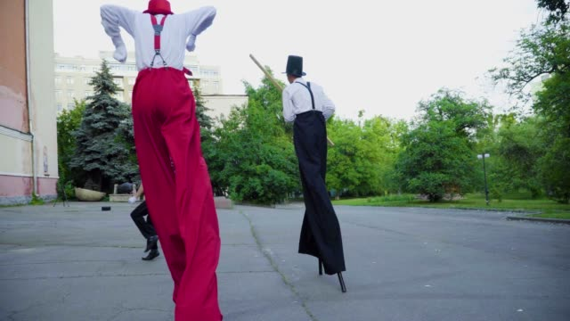 Two stilts chasing mime on the street Two stilts in white shirts and red and black wide pants with mime do performance at the street. Tall actors run in funny way after small colleague around in circles. Artists laughting and have a fun. Performance of street artists actor stock videos & royalty-free footage