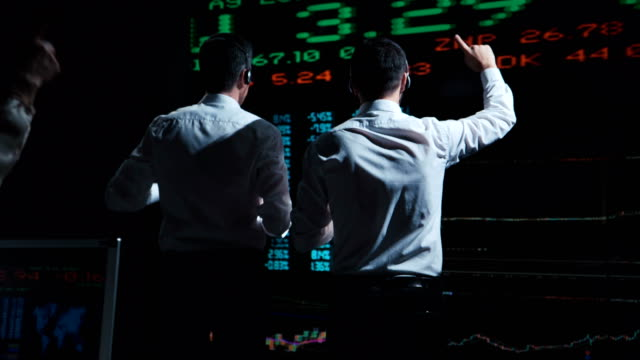 Two stock brokers in front of live market feed video