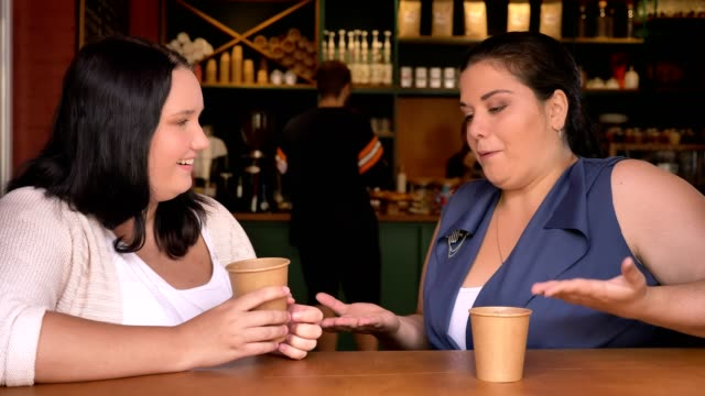 vídeos de stock e filmes b-roll de two stout caucasian girls having conversation hoding coffee in cafe on the table - corpulento