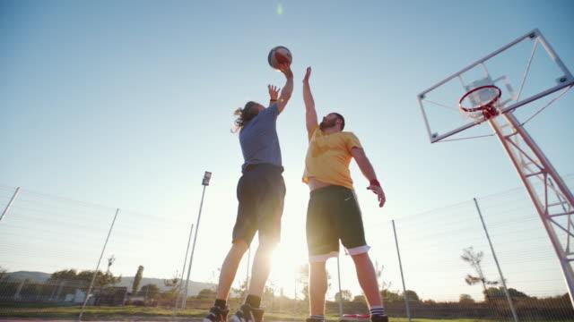 due giocatori di basket in strada in campo - lega sportiva amatoriale video stock e b–roll